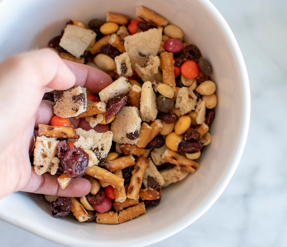 Bowl full of Chocolate Chip Shortbread Cookies, dried cranberries, roasted & salted peanuts, pretzels and Sun Drops