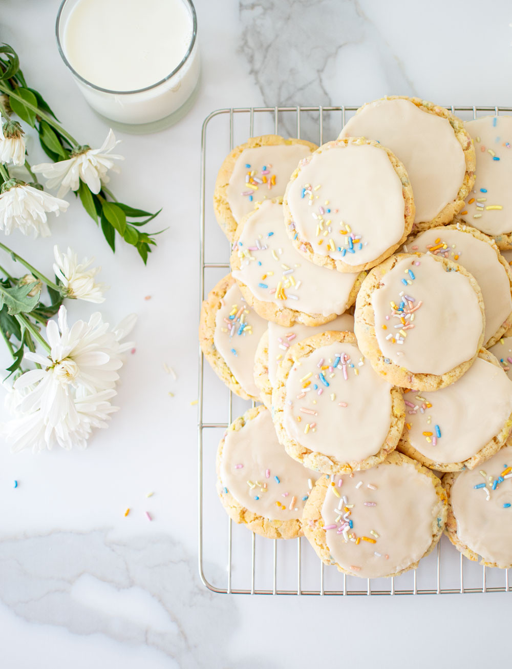 Easy and delicious soft and chewy Funfetti Sugar Cookie recipe with icing. These funfetti cookies use naturally colored sprinkles with no artificial colors. Soft and chewy cookies topped with a sweet icing and more rainbow sprinkles for the perfect funfetti cookies recipe #organiccookies #rainbowsprinkles #funfetti #funfetticookies #softandchewycookies #icingcookies