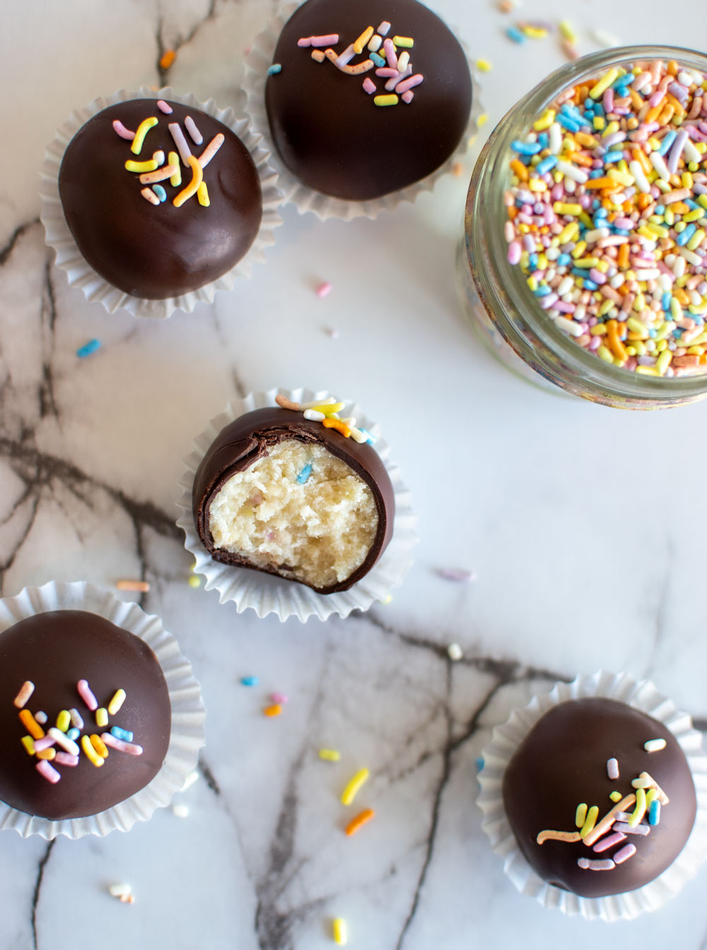 Easy Dark Chocolate Funfetti Cake Ball recipe for New Year's! In this post I'll show you how to make cake balls. These little magical dessert bites are so good, you'll want to bake them all the time! #cakeballs #organic #funfetti #darkchocolate #cake #newyears