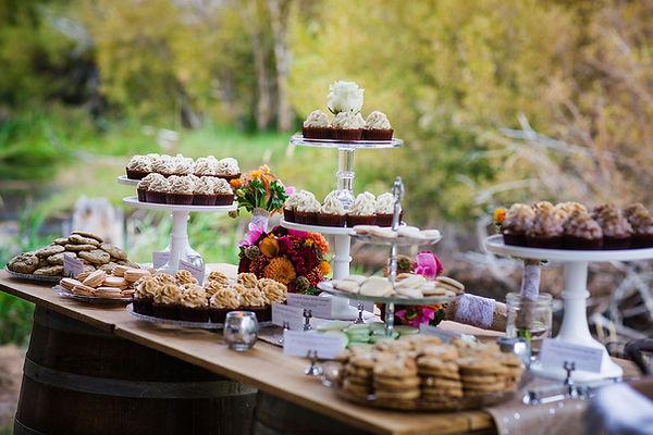 Organic wedding dessert bar set up outside on a rustic table display