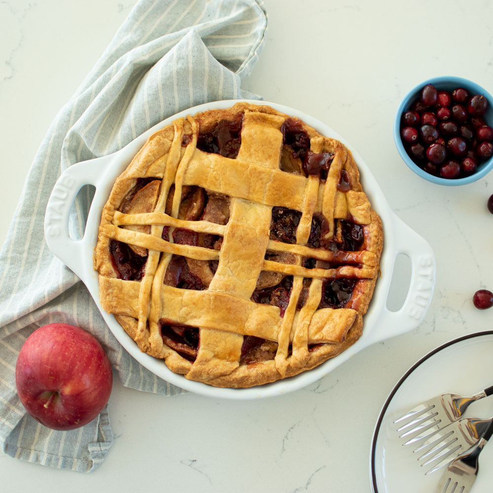 From scratch recipe for Cranberry Apple makes a perfect Christmas pie! This easy butter pie dough makes delicious flaky crust. The filling is apples, cranberries, and warm spices like cinnamon and cloves. This Christmas pie is filled with healthy fresh fruit and is one the whole family will love #pie #organic #organicpie #highaltitudebaking #cranberry #apple #applepie #holidaypie