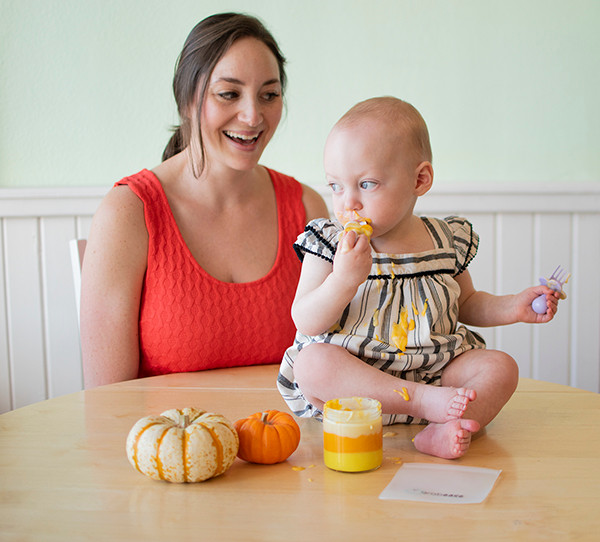 Baby eating Candy Corn Pudding from jar on the table