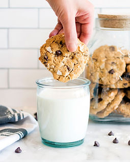 Dad's Coconut Chocolate Chip Cookie being dipped into milk with cookie jar in background