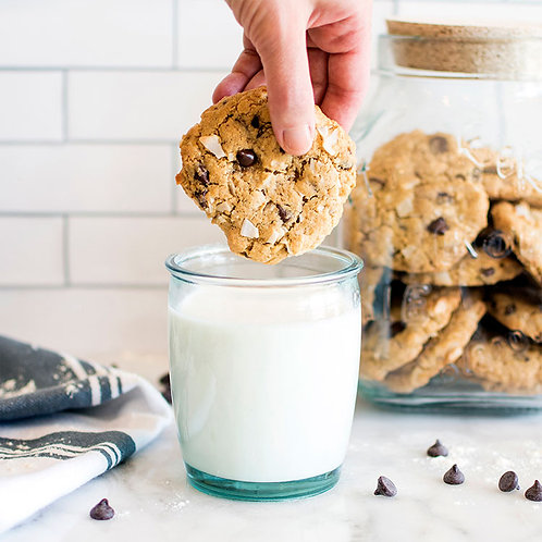 Dipping Coconut Chocolate Chip Cookies in glass of milk