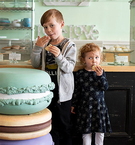 Kids eating cookies in front of the pastry case in the bakery