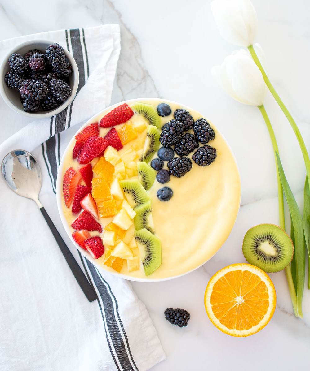 Delicious and easy Rainbow Smoothie Bowl using fresh fruits. This healthy smoothie bowl recipes uses bananas, mangos, and yogurt and it's topped with rainbow fruits like strawberries, orange, pineapple, kiwi, blueberries and blackberries. You'll love this healthy breakfast recipe. #organicfruit #smoothiebowl #smoothies #smoothierecipe #rainbowfruits