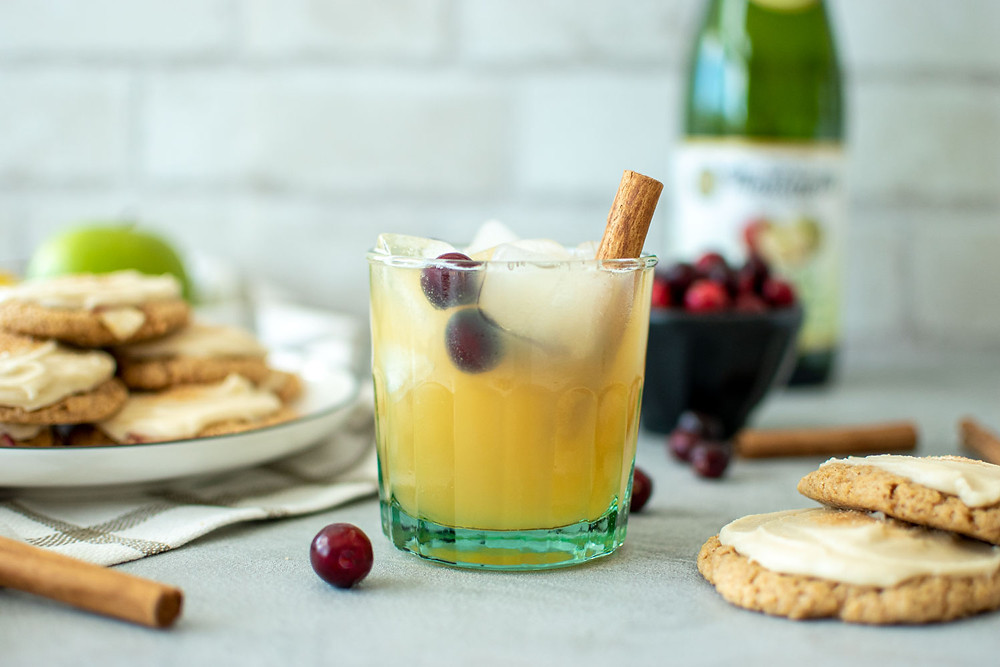 The best Thanksgiving cocktail for a crowd! This Thanksgiving Punch is festive and delicious. Pear juice, sparkling apple cider, and fresh cranberries make this cocktail perfect for Thanksgiving. Add a cinnamon stick for garnish and you have a sweet and spicy cocktail that everyone will love #cocktail #punch #punchbowl #thanksgiving #thanksgivingcocktail #freshcranberries #cranberries #cinnamon #punch #mocktail