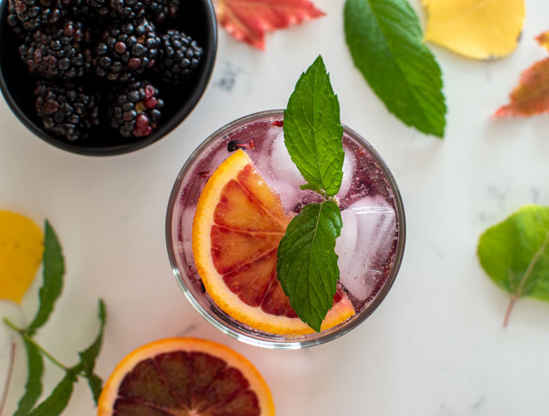 Blood Orange & Blackberry Fizz, the perfect Halloween cocktail recipe. This fall inspired drink can also be made as a mocktail using in season blood oranges and fresh blackberries, topped with fresh mint #mint #freshmint #cocktail #seltzer #mocktail #fizz #halloween #halloweencocktail