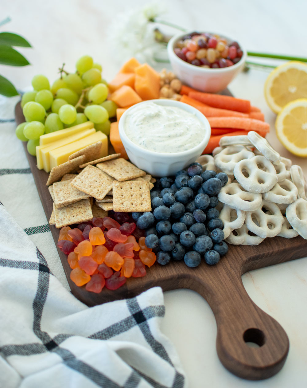 Easy Easter Cheeseboard recipe filled with cheese, fruits, veggies, and Easter candy. This simple cheeseboard recipe is so easy to make and perfect for an Easter appetizer or snack. It uses Easter candy along with a yummy homemade Dill Dip, crackers, cheese, and fruits and veggies. #organiceastercandy #organiccandy #cheeseboard #organiccheese #organicfruits #organicveggies #easycheeseboard #eastersnacks #appetizer #easterrecipe