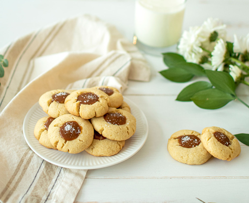 Sweet and salty Chocolate Salted Caramel Thumbprint Cookie recipe that you're sure to love! This easy thumbprint cookie recipe is filled with homemade salted caramel and pure organic milk chocolate. This delicious cookie recipe is sure to impress everyone. #organic #thumbprints #organiccookies #cookies #milkandcookies #saltedcaramel #chocolatecaramel #cookierecipe #cookierecipes