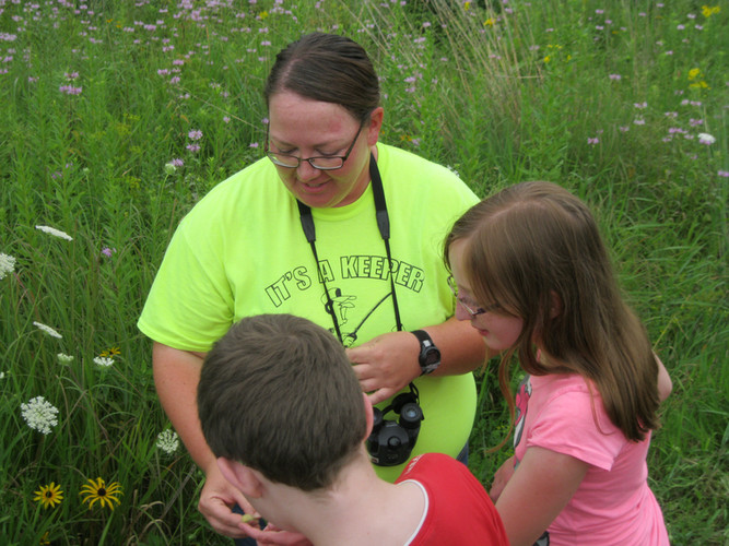 Joni Denker, G-RAS's Program Chair and Resident Ecologist, shows children a plant during a Guided Hike at Spring Creek Reserve.