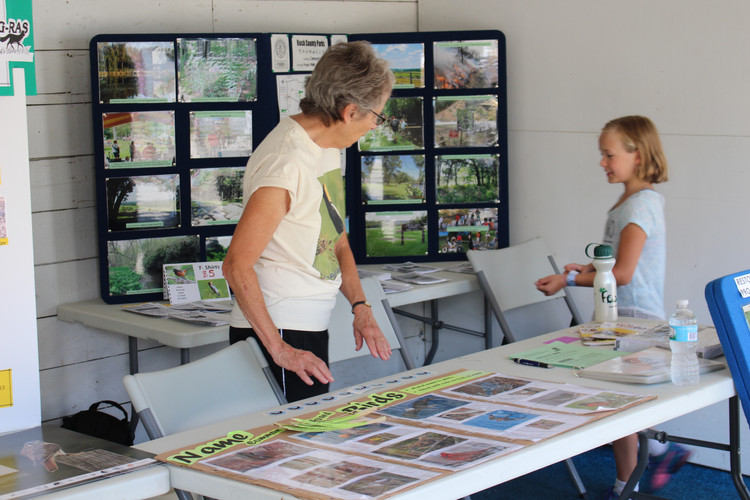 Two volunteers prepare an educational birding game at the Rock County Fair.
