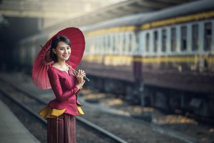 Traveler Asia girl wear traditional dress with umbrella waits for train on railway platform, Bangkok, Thailand