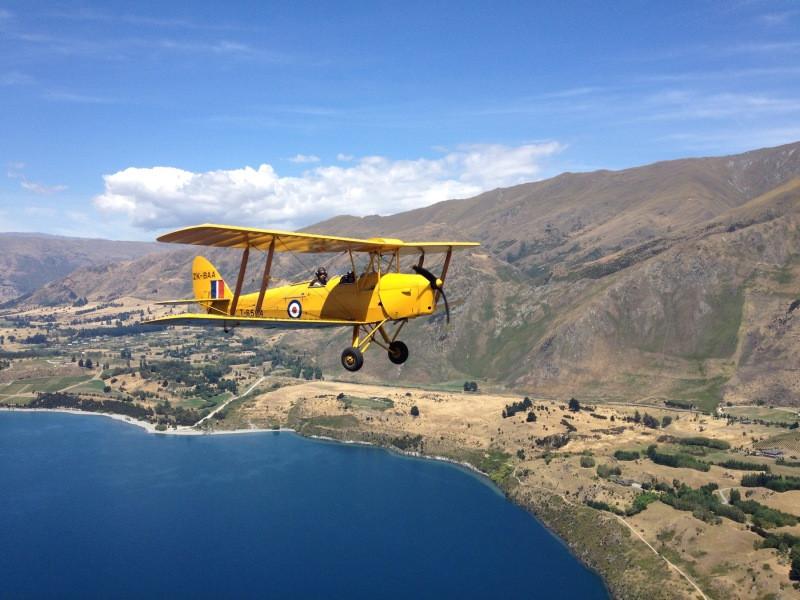Tigermoth flying over Wanaka Lake
