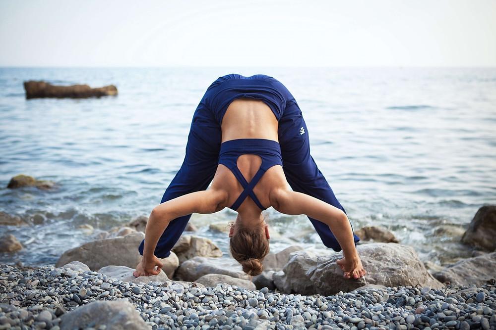 Female Triathlete doing yoga pose near open water