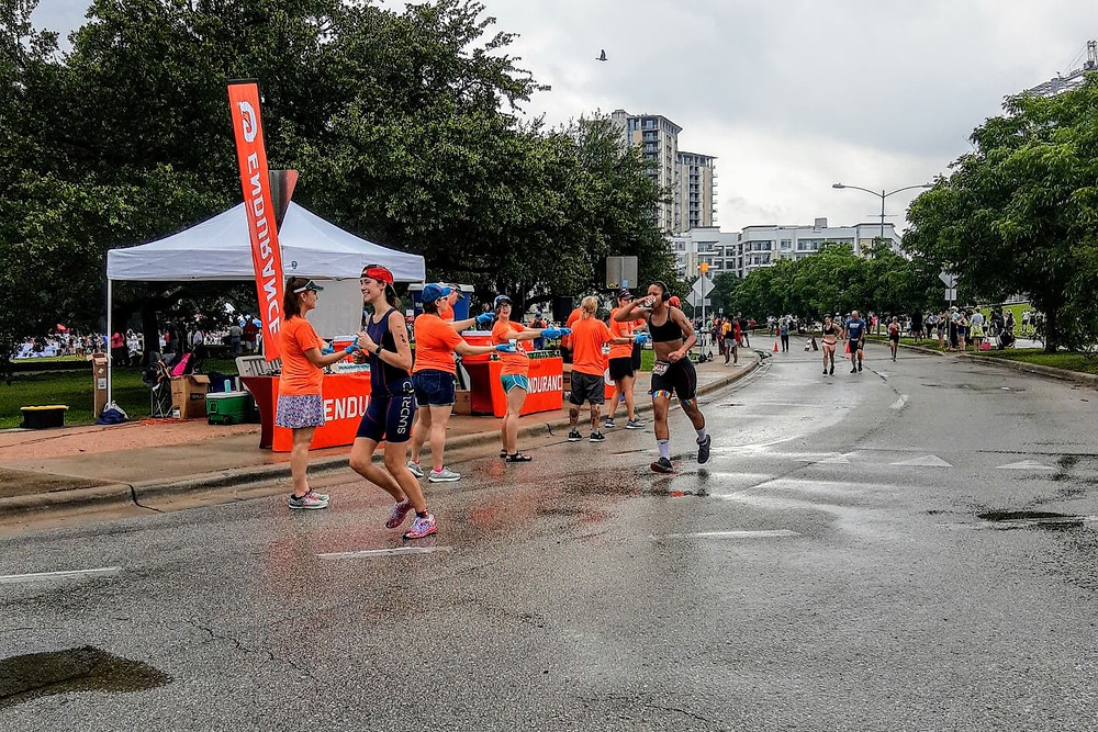 Runners Passing Aid Station in Triathlon Race