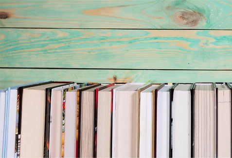 pile-of-miniature-books-on-wooden-backgr