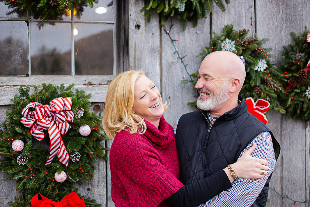 couple laughing surrounded by Christmas wreaths