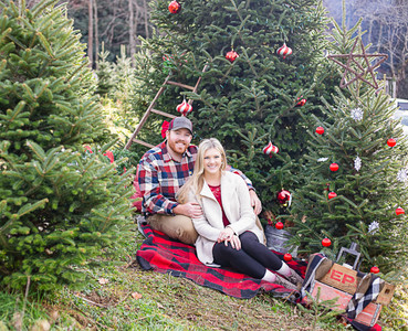couple snuggling in Christmas trees