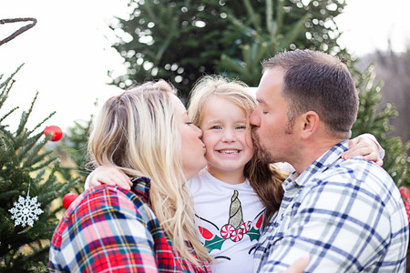 mom and dad kissing little girl cheeks