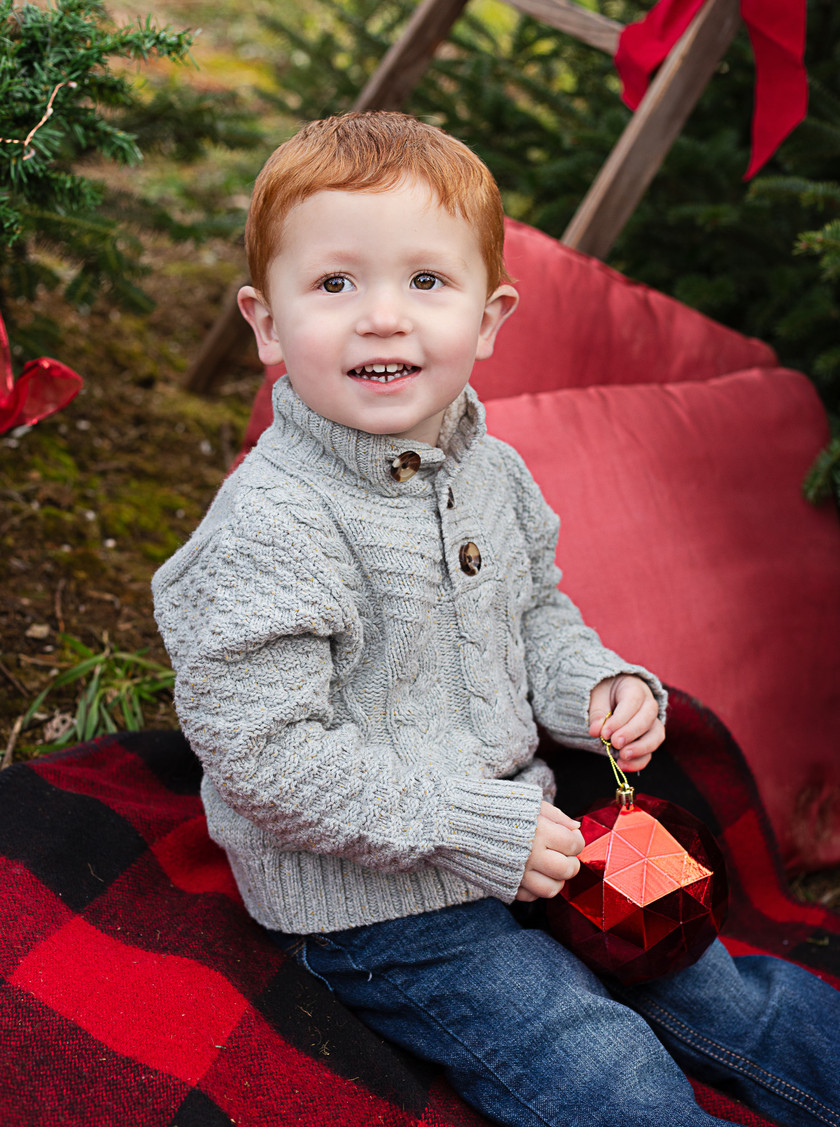 little boy holding red ornament