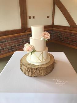 Blush pink wedding cake with geometric gold pattern