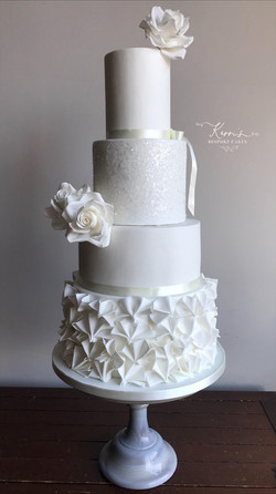 white cake with roses and ruffles