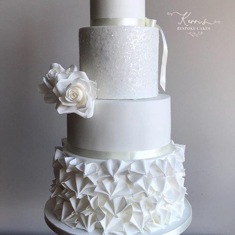 All white cake with sparkles, ruffles and roses