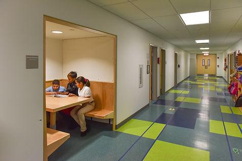 A teacher helps students study in a modular built school