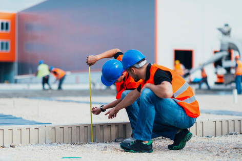 two construction workers measuring