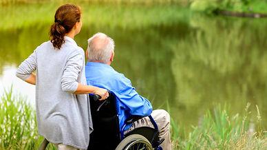 Mujer cuidando a hombre anciano en silla de ruedas