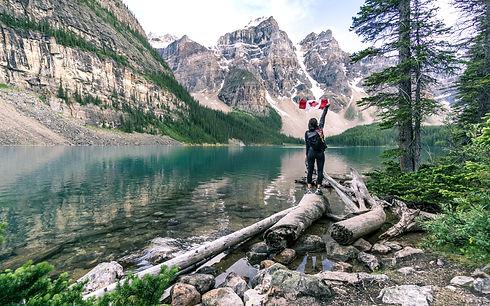 Mujer en paisaje con montañas nevadas y bandera de Canada