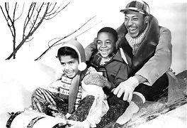 Black family riding a sledge at Christmas.
