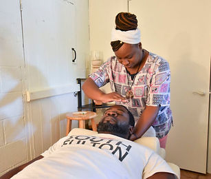 Zura Holmes performing Reiki on Dante' Franklin The Bath House Herbal Health & Wellness