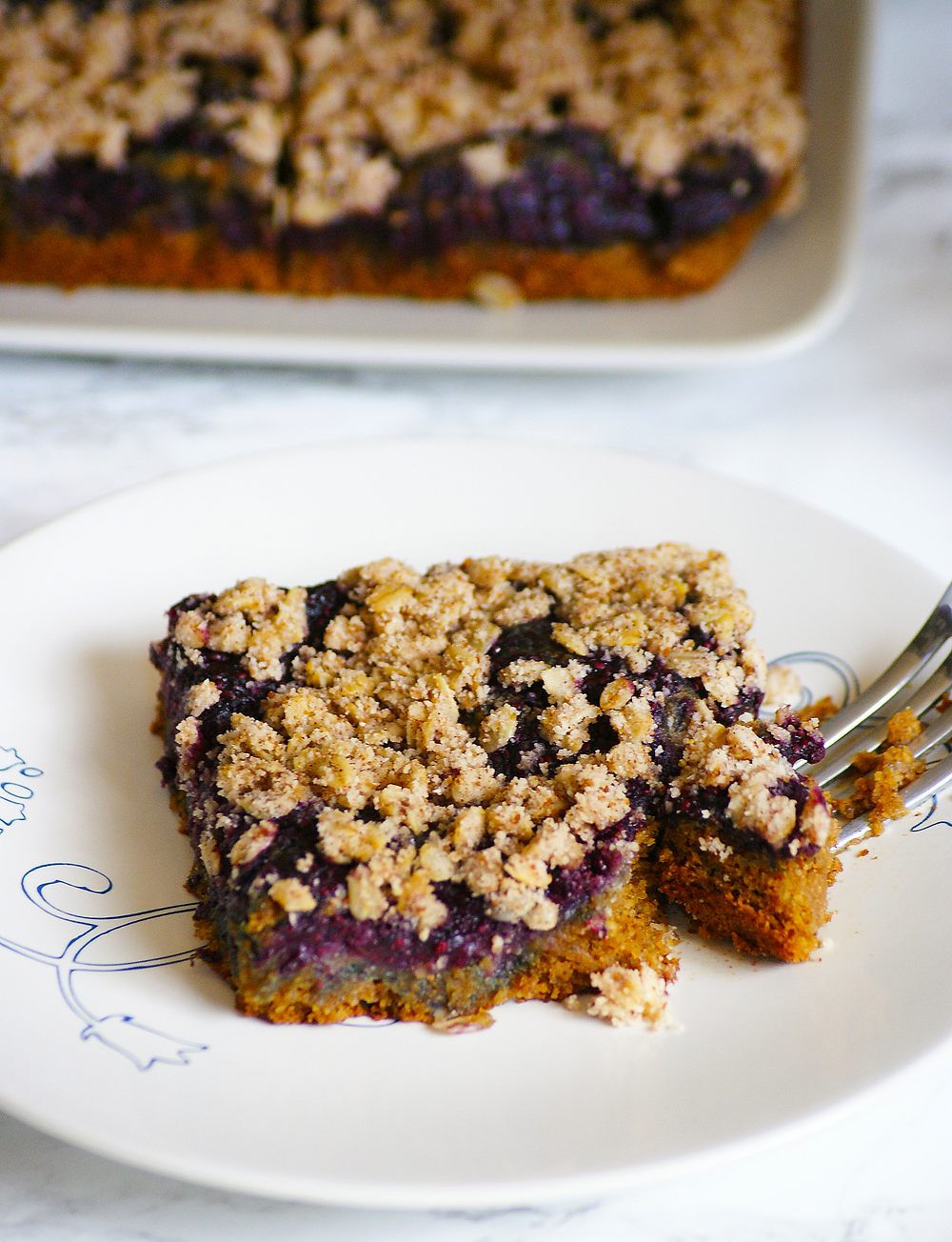 Sice of cinnamon coffee cake with blueberry jam