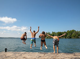 Image of kids jumping into water at Wolfe Island Lodge