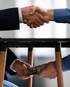 Businessman taking bribe from man under