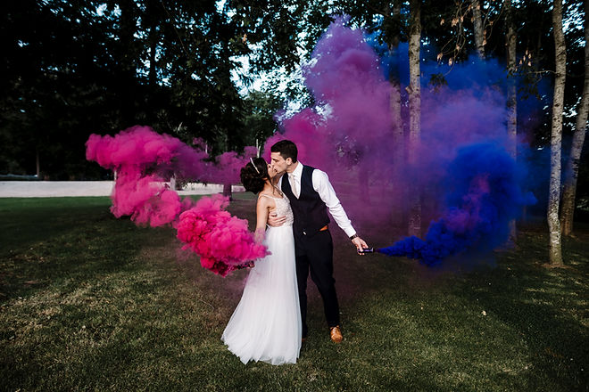 Couple kiss with pink and blue smoke bombs. Image by Amy Faith Photography