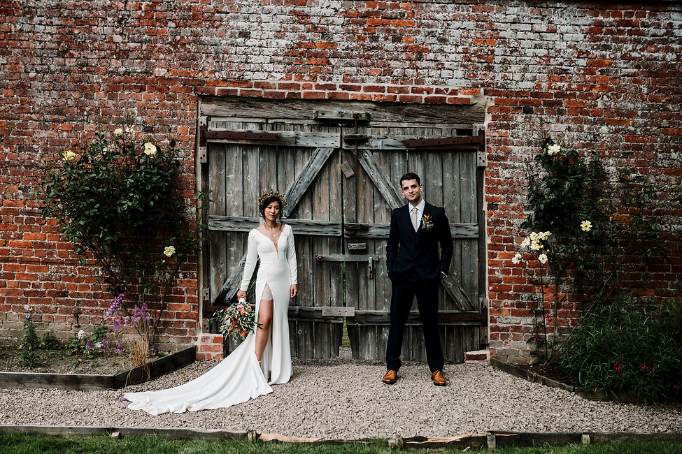 Bride and groom stand in front of a walled garden. Bride wears an ivory dress with a thigh high slit and a gold crown.