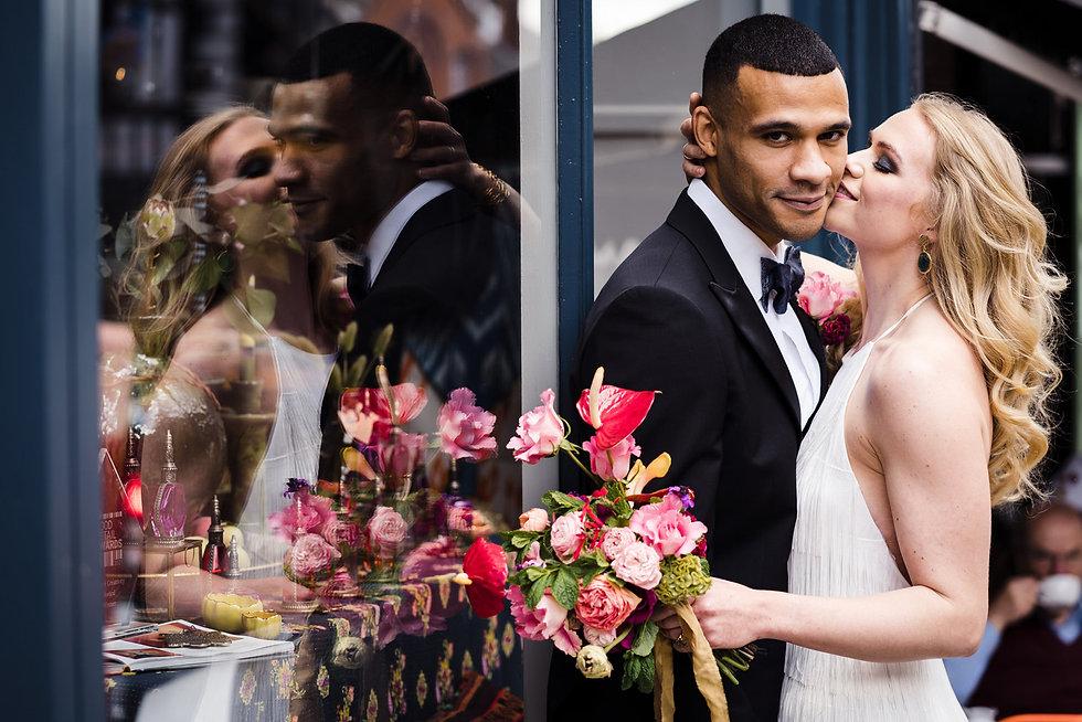 Just married couple embrace. Groom wears a black tuxedo, bride wears a short fringed ivory dress from Charlie Brear.