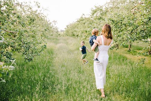 séance photo lifestyle pommier nature famille enfant champs bébé garçon jumpsuit blanc printemps