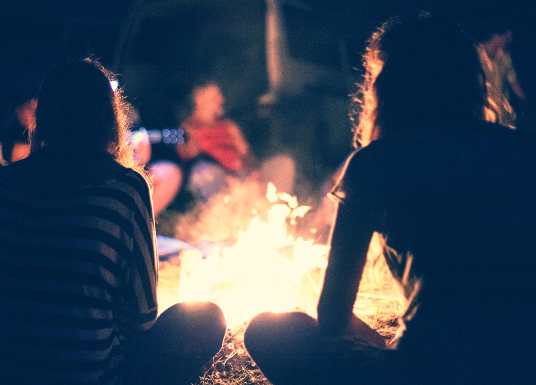 People sit at night round a bright bonfi