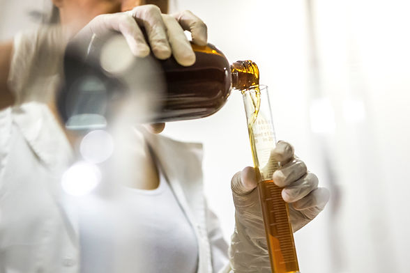 Chemist mixing oils in a beaker