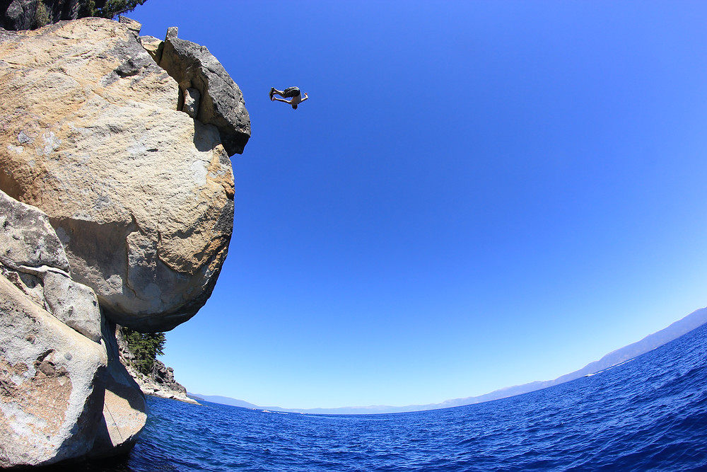 man jumping off of a cliff into a lake