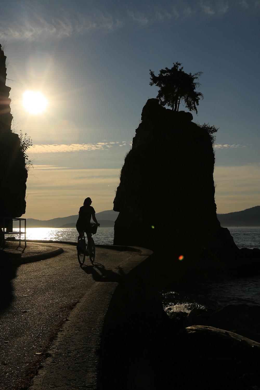 Girl biking along sea wall bike path in Stanley Park