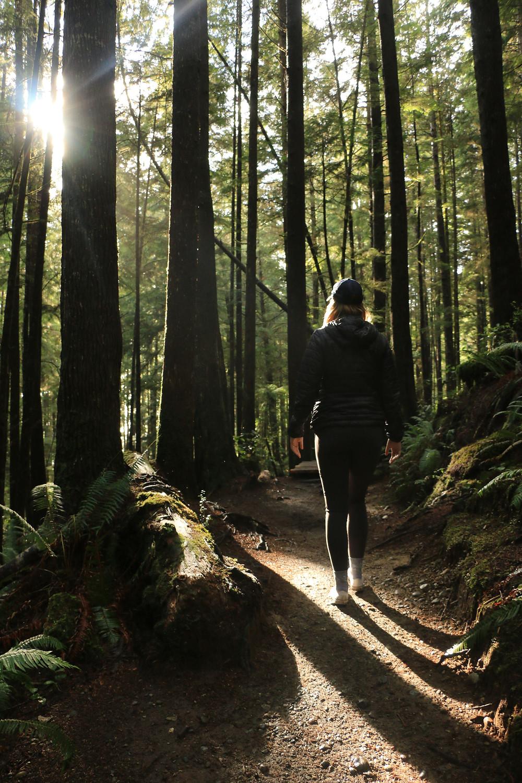 Girl walking through woods on Juan de Fuca trail
