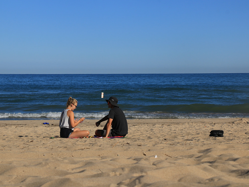 two people eating breakfast on a beach