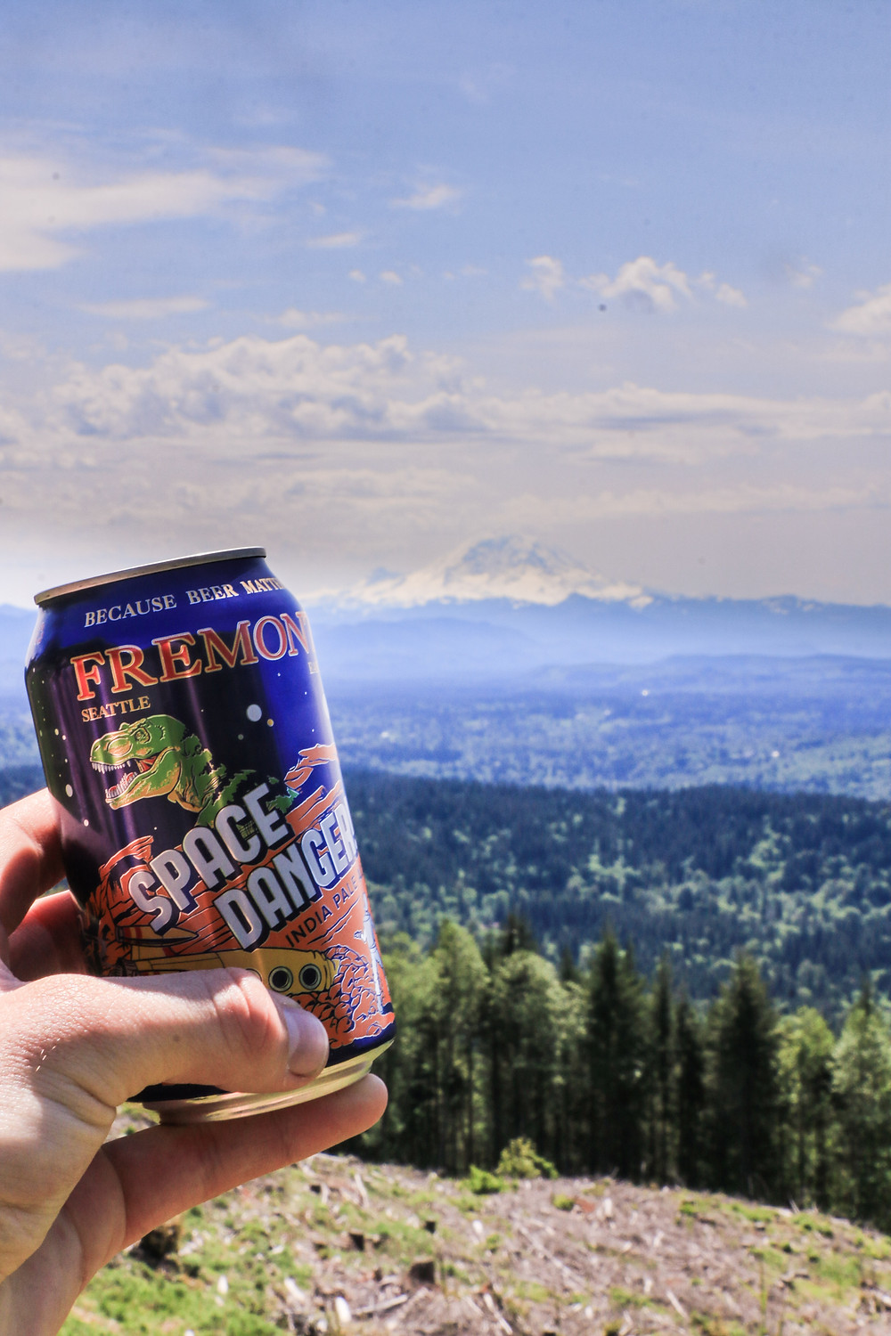 Man holding beer can with Rainier in the background