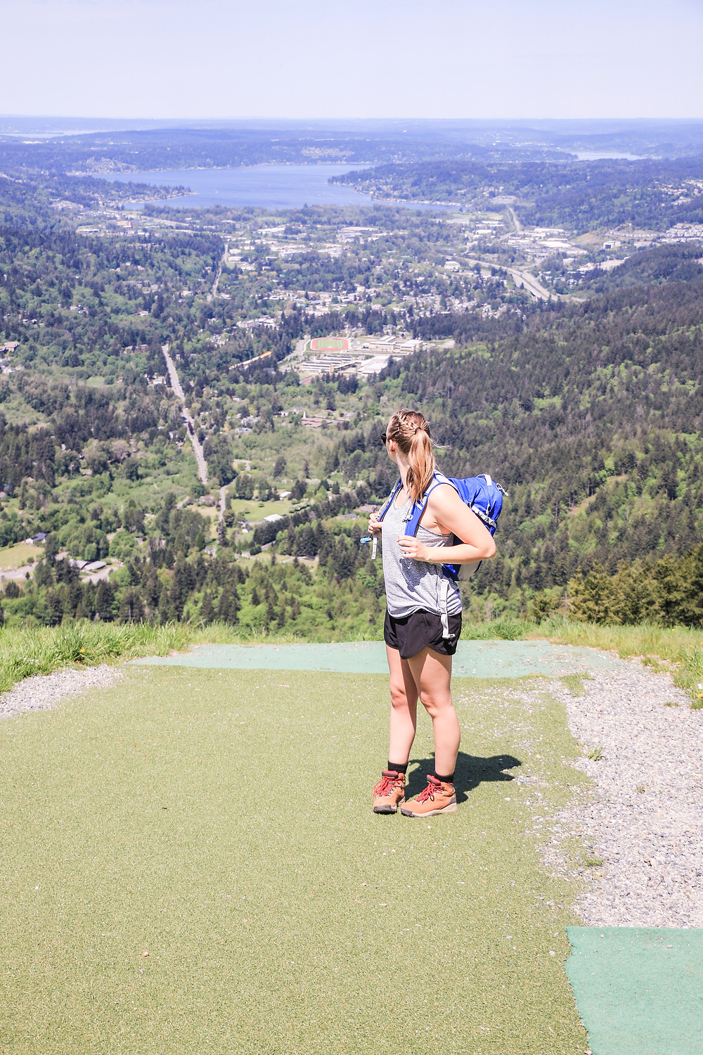 Woman standing on edge of cliff at poo poo point overlooking lake sammamish