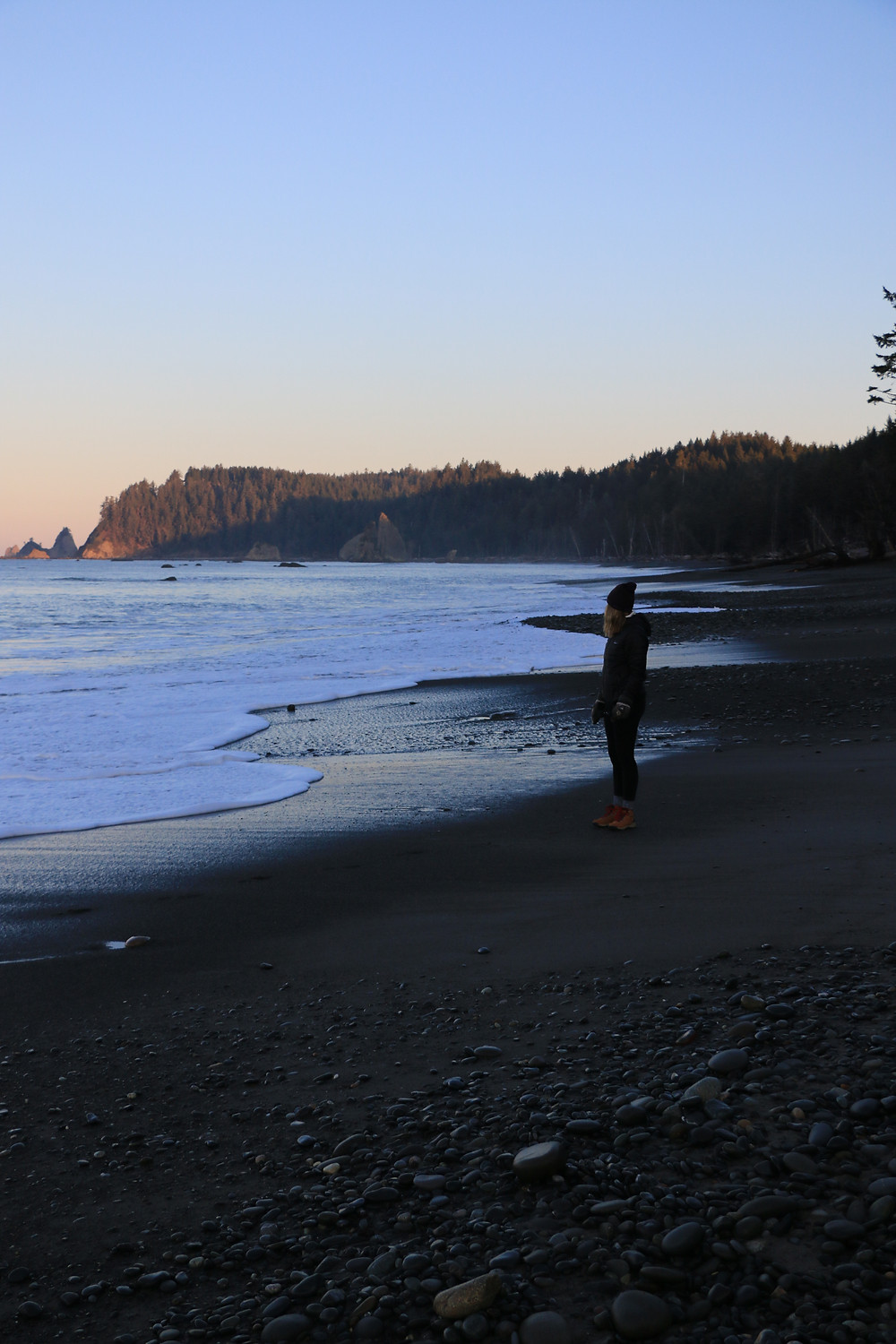 Girl standing on rialto beach during sunrise